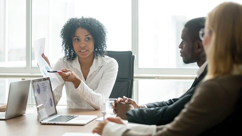 Mitarbeiter diskutieren über gedrucktes Tabellenblatt