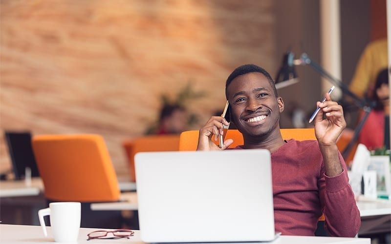 Mann lächelt mit Computer